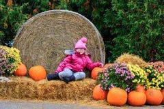 Szczęśliwa mała dziewczynka w Dyniowej łacie dla Halloween lub spadku photoshoot obraz stock