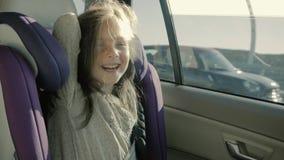 Szczęśliwa mała dziewczynka w samochodzie przy dziecka siedzeniem robi twarzom i śmiać się zbiory