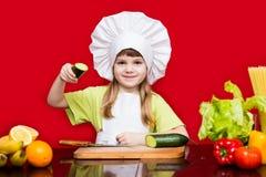Szczęśliwa mała dziewczynka w szefa kuchni mundurze ciie warzywa w kuchni Dzieciaka szef kuchni Zdjęcia Royalty Free