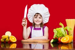Szczęśliwa mała dziewczynka w szefa kuchni mundurze ciie warzywa w kuchni Dzieciaka szef kuchni Obrazy Royalty Free
