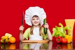 Szczęśliwa mała dziewczynka w szefa kuchni mundurze ciie warzywa w kuchni Dzieciaka szef kuchni Fotografia Royalty Free