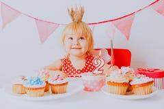 Szczęśliwa mała dziewczynka z cukierkami przy przyjęciem urodzinowym zdjęcie stock