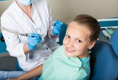 Szczęśliwa mała dziewczynka z otwartym usta przechodzi stomatologicznego traktowanie przy kliniką Dentysta sprawdzać i leczy zęby Fotografia Stock