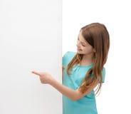 Szczęśliwa mała dziewczynka z pustą białą deską obraz royalty free