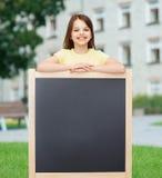 Szczęśliwa mała dziewczynka z pustym blackboard Obrazy Stock