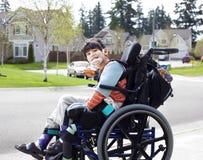Szczęśliwa mała niepełnosprawna chłopiec w wózku inwalidzkim Obraz Royalty Free