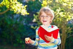 Szczęśliwa mała preschool dzieciaka chłopiec z szkłami, książkami, jabłkiem i plecakiem na jego pierwszy dniu, szkoła lub pepinie zdjęcie stock