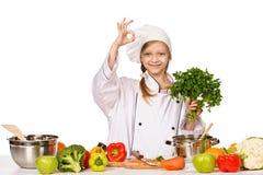 Szczęśliwa mała szef kuchni dziewczyna z pietruszką pokazywać MAŁY Zdjęcie Stock