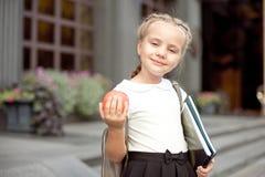 Szczęśliwa mała uczennica z blondynem w mundurku szkolnym z lunchem, książka siedzi blisko szkoły fotografia royalty free