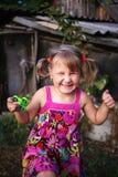 Szczęśliwa mała wiejska dziewczyna z kądziołkiem w jej ręce zdjęcia royalty free