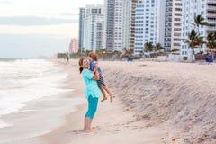 Szczęśliwa małe dziecko chłopiec, matka ma zabawę i na plaży ocean i na burzowym dniu Zdjęcia Stock