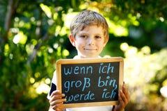 Szczęśliwa małe dziecko chłopiec z kredowym biurkiem w rękach Zdrowy uroczy dziecko outdoors Na biurku chce być wewnątrz Gdy r up zdjęcie stock