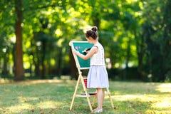Szczęśliwa małe dziecko dziewczyny pozycja dużym kredowym biurka schoolkid na pierwszy dniu podstawowa klasa lub Preschool tylna  obrazy royalty free