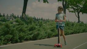 Szczęśliwa małej dziewczynki jazdy kopnięcia hulajnoga w parku zbiory wideo