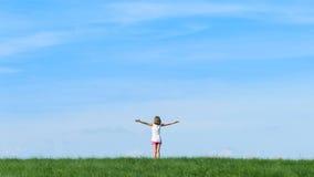 Szczęśliwa małej dziewczynki pozycja w polu na niebieskiego nieba tle Obrazy Stock