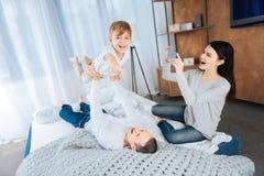 Szczęśliwa macierzysta ekranizacja jej syna naśladowania bohater podczas gdy bawić się obrazy stock