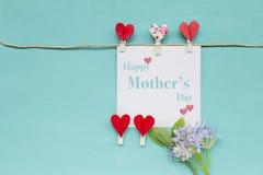 Szczęśliwa Macierzysta ` s dnia karta z czerwoną kierową klamerką i kwiatem na błękitnym tekstury tle Obraz Stock