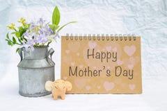 Szczęśliwa Macierzysta ` s dnia wiadomość na pustej brown notatnik pokrywie z kwiatu garnkiem i uśmiechniętego słonia glinianą la Zdjęcia Royalty Free