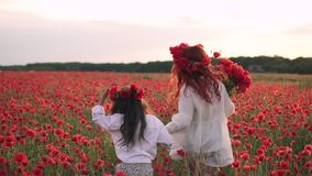 Szczęśliwa mama i córka biegamy przez kwitnącego maczka pola przy zmierzchem, tylni widok, zwolnione tempo zbiory