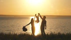 Szczęśliwa mama i tata jesteśmy na krawędzi falezy i podnosimy jej córki ` s ręki przeciw zmierzchowi i morzu zbiory wideo