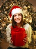 Szczęśliwa marzycielska kobieta z prezentem na nowego roku drzewa dekoracji w domu fotografia stock