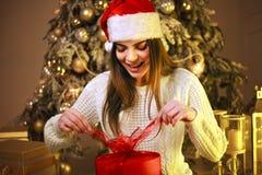 Szczęśliwa marzycielska kobieta z prezentem na nowego roku drzewa dekoracji w domu obrazy stock