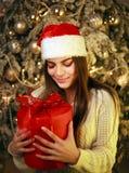Szczęśliwa marzycielska kobieta z prezentem na nowego roku drzewa dekoracji w domu zdjęcie royalty free