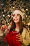 Szczęśliwa marzycielska kobieta z prezentem na nowego roku drzewa dekoracji w domu zdjęcia stock