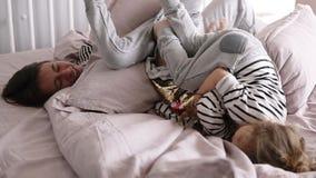 Szczęśliwa matka bawić się wraz z jej dwa córkami w łóżkowym robi bałaganie w zwolnionym tempie zbiory wideo