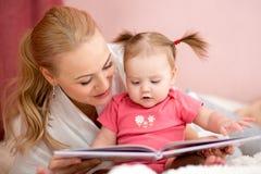 Szczęśliwa matka czyta książkę dziewczynka zdjęcia royalty free