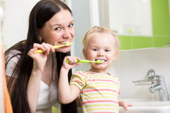 Szczęśliwa matka i córka żartujemy dziewczyny szczotkuje zęby zdjęcia royalty free