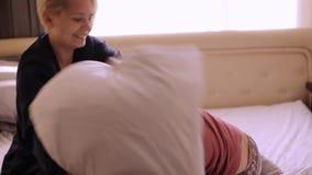 Szczęśliwa matka i córka ma poduszki walkę w łóżku w domu zbiory