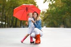 Szczęśliwa matka i córka z czerwonym parasolem zdjęcia stock