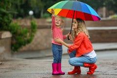 Szczęśliwa matka i córka z jaskrawym parasolem zdjęcie stock