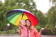 Szczęśliwa matka i córka z jaskrawym parasolem pod deszczem obrazy royalty free