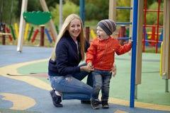 Szczęśliwa matka i chłopiec bawić się na boisku Obrazy Royalty Free