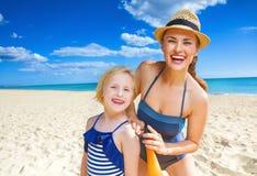 Szczęśliwa matka i dziecko na seashore stosuje suntan płukankę Obrazy Stock