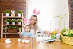 Szczęśliwa matka i jej śliczny dziecko jest ubranym królików ucho, dostaje przygotowywający dla wielkanocy obrazy royalty free