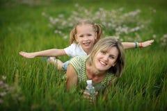 Szczęśliwa matka i jej córka bawić się w trawie Obrazy Royalty Free