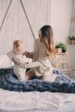 Szczęśliwa matka i 8 miesięcy stary dziecko bawić się w domu i relaksuje w sypialni w ranku Zdjęcie Stock