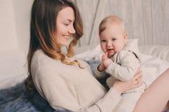 Szczęśliwa matka i 8 miesięcy stary dziecko bawić się w domu i relaksuje w sypialni w ranku Obrazy Royalty Free