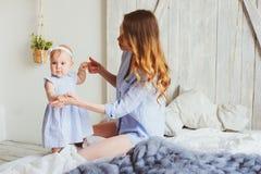 Szczęśliwa matka i 9 miesięcy stary dziecko w dopasowywanie piżamach bawić się w sypialni w ranku Zdjęcie Stock