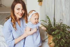 Szczęśliwa matka i 9 miesięcy stary dziecko w dopasowywanie piżamach bawić się w sypialni w ranku Zdjęcia Stock