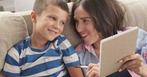 Szczęśliwa matka i syn pisze robić liście w notepad zbiory