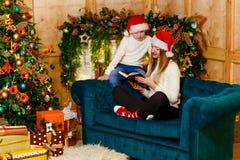 Szczęśliwa matka i syn w dopasowywanie pulowerach czyta książkę na leżance blisko graby dla bożych narodzeń zdjęcia stock