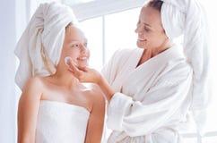 Szczęśliwa matka pomaga jej córki czyścić twarz Obraz Stock
