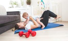 Szczęśliwa matka robi ćwiczeniu w domu i ma zabawę z jej dzieckiem Obraz Royalty Free