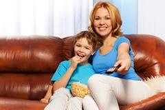Szczęśliwa matka siedzący ogląda TV i dziecko Zdjęcia Royalty Free