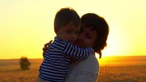 Szczęśliwa matka trzyma jej dziecka w jej rękach, być na pszenicznym polu wśród zmierzchu Pojęcie szczęśliwa rodzina zdjęcie wideo