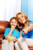 Szczęśliwa matka wskazuje naprzód i syna zegarek TV Obrazy Royalty Free